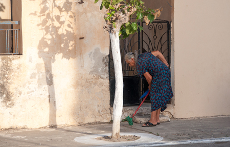 scavenge: Early morning in Paleochora on Crete. Grandma is sweeping the street in front of her house. Paleochora is a nice Village in the south of Crete. Plenty of tourists spend their vacation here