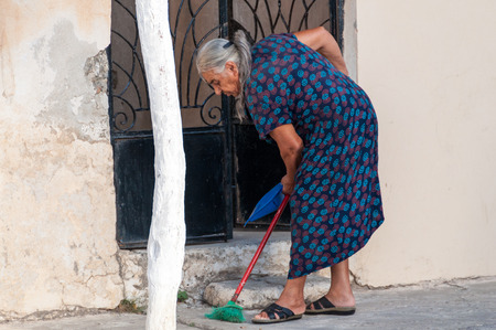 scavenge: Early morning in Paleochora on Crete. Grandma is sweeping the street in front of her house. Paleochora is a nice Village in the south of Crete. Plenty of tourists spend their vacation he Editorial
