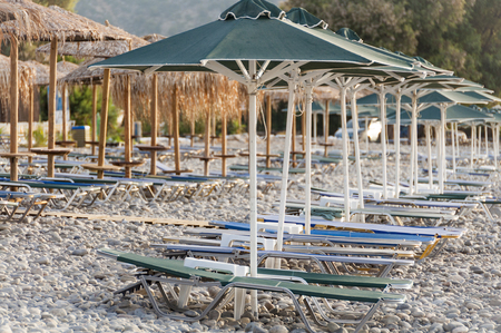 pebble beach: Empty bed chairs on the pebble beach in Paleochora on the south coast of Crete Stock Photo