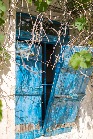 Blue, wooden window shutter in close-up at an abandoned house in the village Paleochora in the south-west of Crete. The house is covered with vine. Stock Photo