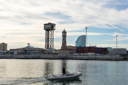 inflatable boat: Man on inflatable boat in front of the shipyards of Port Vell in Barcelona