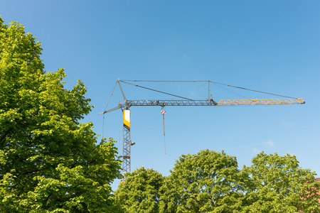 Tower crane on a construction site in Hamburg Altona. The construction site is covert with trees