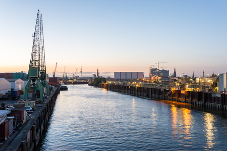Hamburg at sundown. View to the City from the industrial estate harborside. To see is the Hamburg Michaels church the radio telecommunication tower Heinrich Hertz Tower and the Elbe Philharmonic Hall Stock Photo