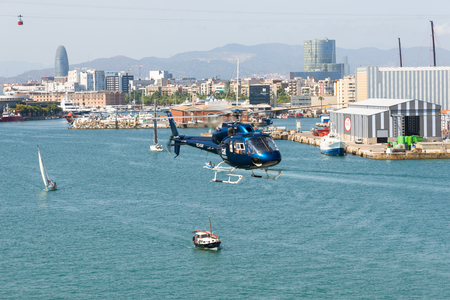 trip over: Helicopter above the harbor of Barcelona. The aircraft is on a round trip over Barcelona