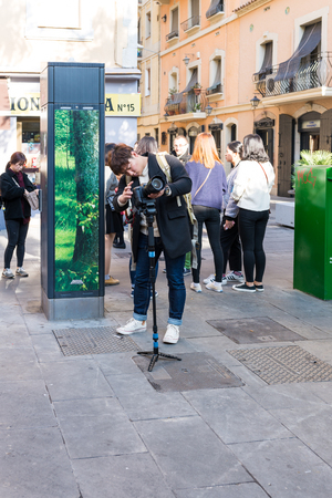 Asian Photographer takes pictures from sightseeing in the Barceloneta district of Barcelona. Barcelona is one of the most visited cities in Europe Banco de Imagens - 93493892