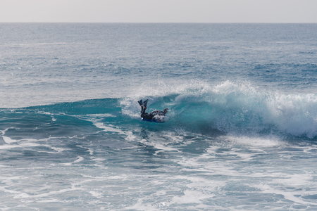 Bodyboarding and surfing on the Atlantic Ocean in front of La Gomera Island. A short light type of surfboard ridden in a perfect position