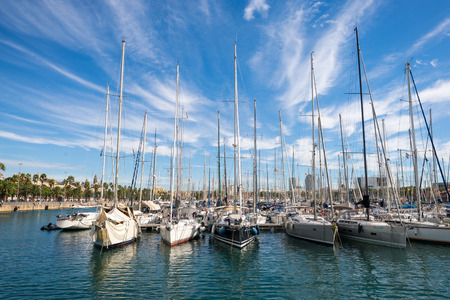 Plenty of sailboats are moored in the harbor of Port Vell in Barcelona. The marina is popular and an important destination for sailing trips Stock Photo
