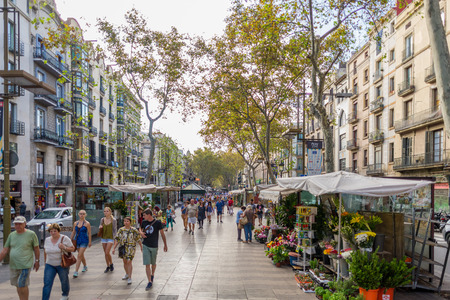 Tourists and residents walk along the Rambla de San Josep on a sunny day in autumn Editorial