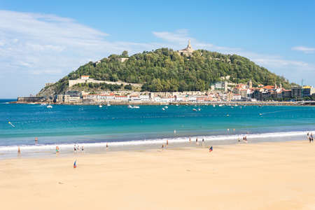 View to the mountain Urgull with the sculpture of Jesus. The beach of La Concha, one of the most famous urban beaches in Europe Standard-Bild - 116663235