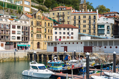 Picturesque houses, fishing boats and sport boats for recreational fishing are moored in the harbor of Donostia San Sebastian Standard-Bild - 116663249