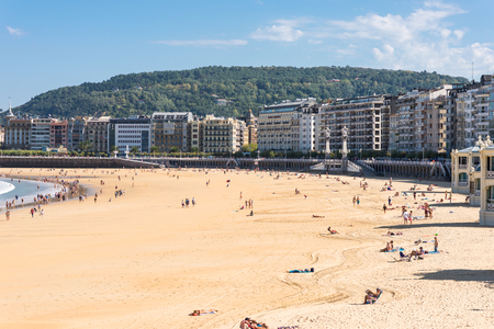 Walking on the beach at La Concha, a sand beach with shallow waters. It is one of the most famous urban beaches in Europe in San Sebastian Standard-Bild - 116663254