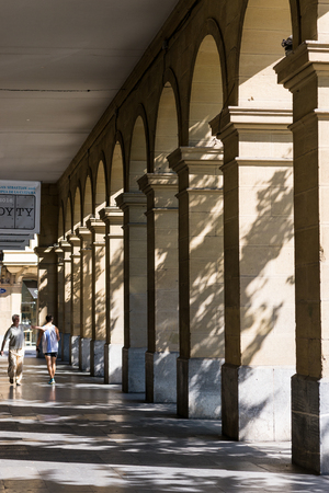 Two man under the colonnade at the San Martin Kalea, one of the main streets in San Sebastian Banco de Imagens - 116663256