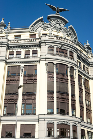 Neoclassical facade with an eagle sculpture on the roof at the Plaza Centenario in Donostia San Sebastian Standard-Bild - 116663264