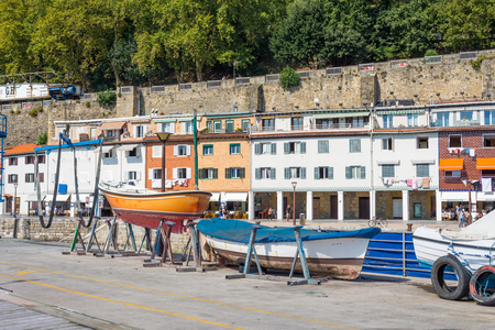 Picturesque houses, fishing boats and sport boats for recreational fishing are moored in the harbor of Donostia San Sebastian. Standard-Bild - 116663279