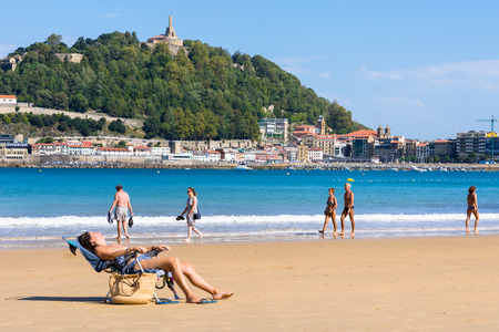 Inhabitants and tourists relax at the beach. La Concha, a sand beach with shallow waters. It is one of the most famous urban beaches in Europe Standard-Bild - 116663282