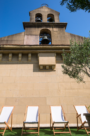 Deckchairs under Bell on a church in Donostia San Sebastian, the Basque Country in Spain Stock Photo