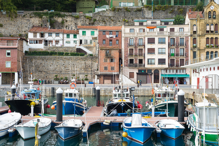 Picturesque houses, fishing boats and sport boats for recreational boat fishing are moored in the harbor of Donostia San Sebastian. The port is located close to the famous bay of La Concha