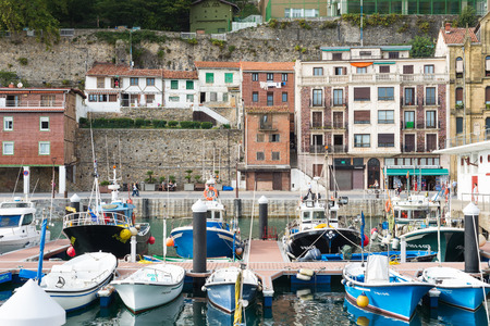 Picturesque houses, fishing boats and sport boats for recreational boat fishing are moored in the harbor of Donostia San Sebastian. The port is located close to the famous bay of La Concha Standard-Bild - 116663309