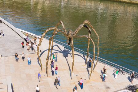 The Maman bronze, stainless steel sculpture from the artist Louise Bourgeois in the city of Bilbao. Town folk, tourists, people enjoying the sunny day at the Nervion river