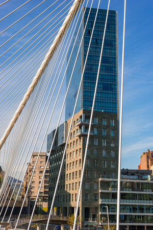 The bridge Puente Zubizuri and the Isozaki Atea, Basque, Isozaki Gate, twin towers in Bilbao, Spain. The high-rise buildings are the tallest residential buildings in the city