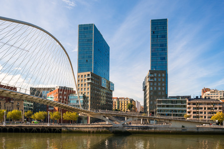 The bridge Puente Zubizuri and the Isozaki Atea, Basque for Isozaki Gate, twin towers in Bilbao, Spain. The high-rise buildings are the tallest residential buildings in the city