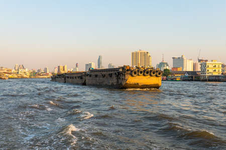 Pusher craft with barges on the Chao Phraya river in Bangkok. The river meanders through the city in southward direction, emptying into the Gulf of Thailand