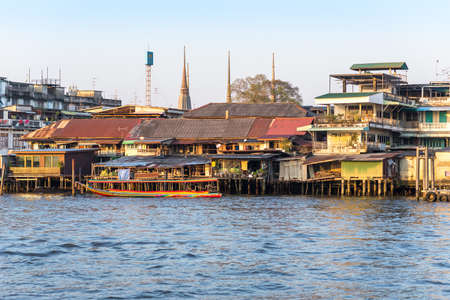Boat in front of stilt houses along the Chao Phraya river in Bangkok
