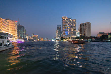 Skyline and pleasure boats at the pier for night cruise on the Chao Phraya river in Bangkok Standard-Bild
