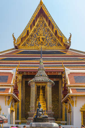 The famous Buddhist temple Wat Phra Kaew, located in the historic center Bangkok. In the foreground, the statue of the Seated Hermit, behind, the statue Phra Phothi That Phima