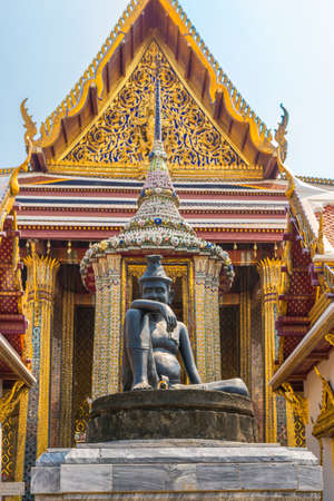 The famous Buddhist temple Wat Phra Kaeo, located in the The Grand Palace in the historic center Bangkok. In the foreground, the statue of the Seated Hermit, behind, the temple of the Emerald Buddha Editorial