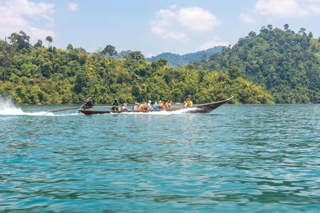 Long-tail boat transport tourists on the Cheow Lan lake in the national park Khao Sok Editorial