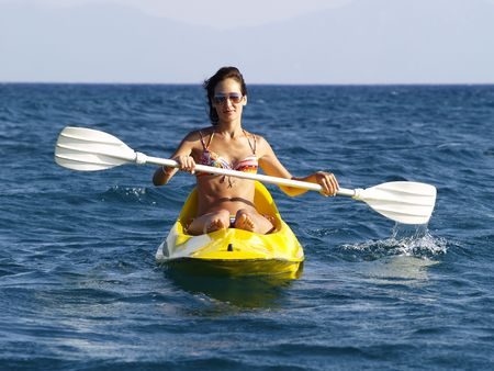 oar: The woman floating on the sea on a kayak with an oar. Stock Photo
