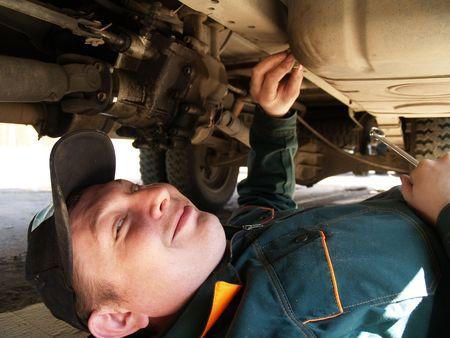 fixing: The professional Mechanic behind work. Lorry repair. Stock Photo