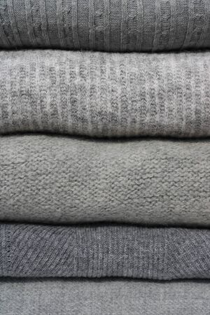 Stack of cozy warm sweaters. Five shades of gray.