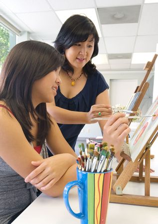 Student and teacher during painting lesson Stock Photo