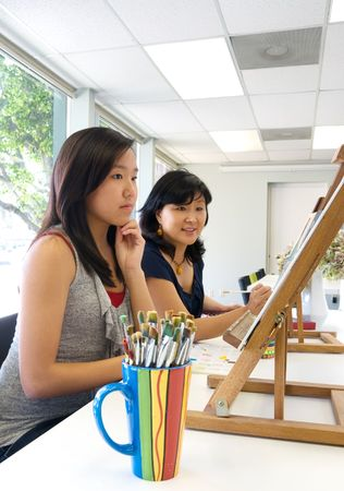 Artists completing art work or student with art teacher