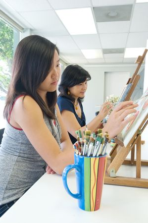 Two people painting in a classroom situation photo
