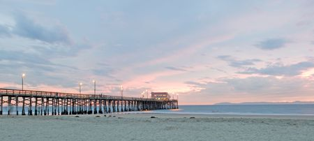 Balboa Pier in Newport Beach at sunset during time lapse so that people appear ghostly