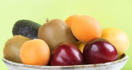 Bowl of fruit on green background