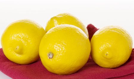 Four bright yellow lemons on a red napkin