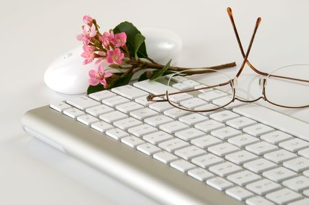 sleek: Sleek, beautiful, ultra modern computer keyboard and mouse with pink flowers and eyeglasses on white background.