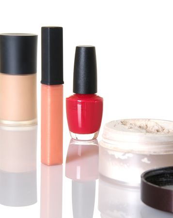 gloss: Cosmetic items including nail polish, foundation, lip gloss, and face powder; focus on left of red bottle