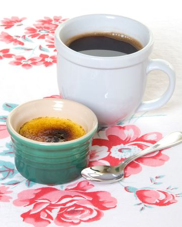Creme Brulee with black coffee on antique tablecloth Stock Photo