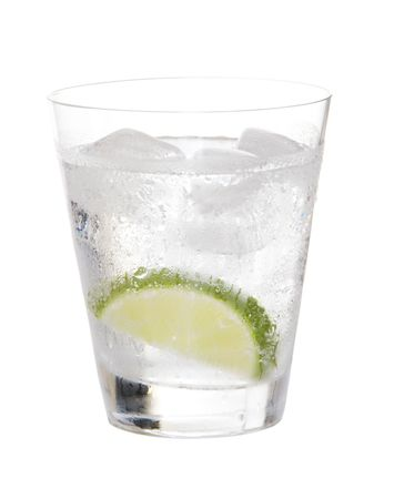 gin: Glass of gin and tonic on ice with lime on white background Stock Photo