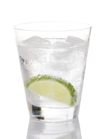 gin: Glass of gin and tonic on ice with lime