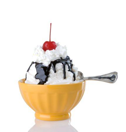 Creamy hot fudge sundae with whipped cream and cherry in bright yellow bowl Stock Photo
