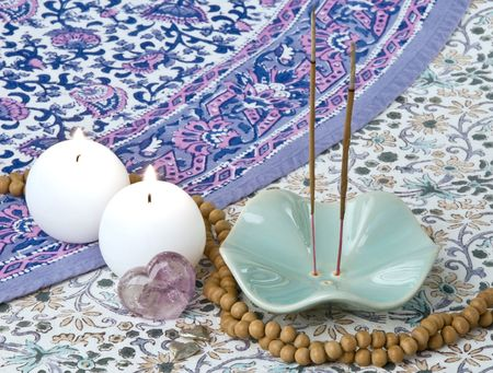 Incense, sandalwood prayer beads, candles, metal hearts, and an amethyst crystal heart on an Indian patterned background in shades of purple, pink, and turquoise. Stock Photo