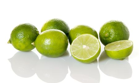 Fresh key limes with one sliced in half on white background with reflection Imagens
