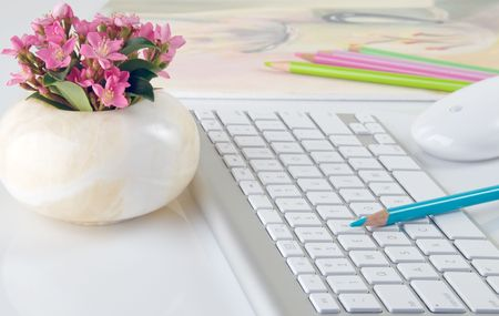 computer education: Beautiful computer keyboard and mouse with fresh flowers in vase, colored pencils, and colorful artwork
