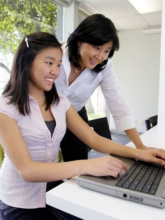Young student learning computer skills with the help of her teacher Stock Photo